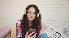 有耳机的少妇,发短信在智能手机 女孩在电话谈话通过录影 妇女以黄色 股票视频