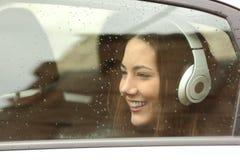 有耳机的少年听到在汽车的音乐的 免版税库存照片