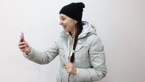 有耳机的少年女孩在耳朵谈话在智能手机的录影电话 股票录像