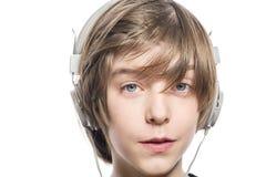 有耳机的少年男孩 免版税库存图片