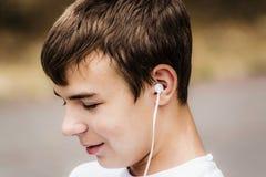 有耳机的少年 免版税库存照片