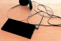 有耳机的巧妙的电话黑色屏幕 库存照片