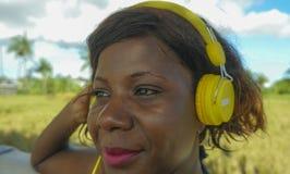 有耳机的年轻美丽和愉快的黑人美国黑人的妇女听到户外音乐的变冷了并且放松了享受夏天 库存照片