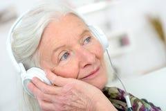有耳机的年长妇女 库存照片