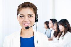 有耳机的微笑的亚裔妇女作为电话推销员、操作员、电话中心和顾客服务概念 免版税库存图片