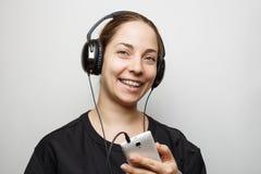 有耳机的微笑的女孩听到从智能手机的音乐的 库存照片