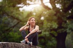 有耳机的快乐的女运动员在公园 免版税库存照片