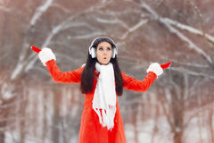 有耳机的惊奇的冬天女孩享用雪的 免版税库存照片