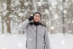 有耳机的愉快的体育人在冬天森林里 免版税图库摄影