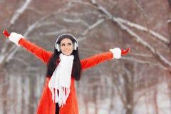 有耳机的愉快的冬天女孩享用雪的 库存照片