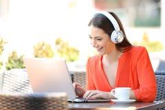 有耳机的愉快的女孩使用一台膝上型计算机在咖啡馆 免版税库存照片