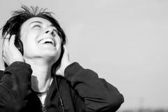 有耳机的愉快的女孩听到在屋顶和微笑的音乐的 图库摄影