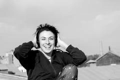 有耳机的愉快的女孩听到在屋顶和微笑的音乐的 免版税库存照片