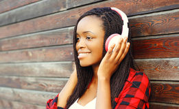 有耳机的愉快的微笑的非洲妇女享用的时尚画象听到在背景的音乐 免版税库存照片