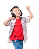 有耳机的愉快的男孩 库存照片