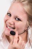 有耳机的愉快,微笑的职业妇女 免版税图库摄影