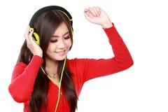 有耳机的愉快的年轻亚裔女孩 免版税库存图片