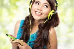 有耳机的愉快的年轻亚裔女孩 库存照片
