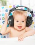 有耳机的愉快的婴孩 图库摄影
