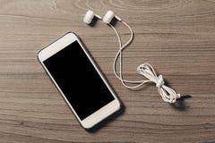 有耳机的手机在木背景 免版税库存照片