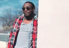 有耳机的时尚画象非洲人听到在城市空的拷贝空间的音乐 免版税库存照片