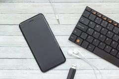 有耳机的智能手机,键盘和闪光在木背景,现代技术的概念驾驶 库存照片