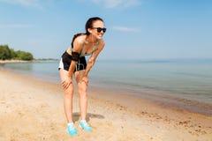 有耳机的母赛跑者和在海滩的臂带子 库存照片