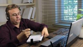 有耳机的用户支持操作员写与笔的信息在笔记本 影视素材