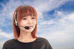 有耳机的电话中心操作员和蓝天和云彩在bac中 免版税库存图片