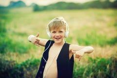 有耳机的男孩听到音乐的本质上 库存图片