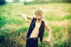 有耳机的男孩听到音乐的本质上 免版税库存照片
