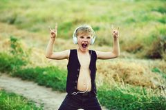 有耳机的男孩听到音乐的本质上 免版税库存图片