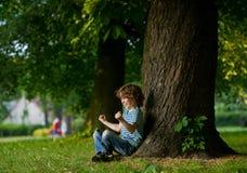 有耳机的男孩在耳朵坐在一棵大树下 免版税库存照片