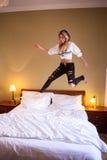 有耳机的疯狂的少妇在床上跳 免版税库存图片