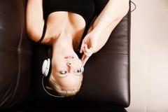 有耳机的白肤金发的女孩 免版税库存照片