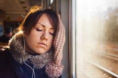 有耳机的睡觉的女孩在火车 免版税库存照片