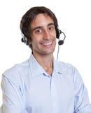 有耳机的笑的西班牙操作员 库存照片