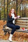 有耳机的红头发人女孩在城市公园听在球员的音乐,秋季 图库摄影