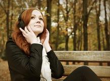 有耳机的红头发人女孩在城市公园听在球员的音乐,秋季 免版税库存图片