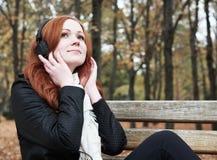 有耳机的红头发人女孩在城市公园听在球员的音乐,秋季 库存照片