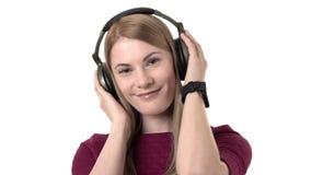 有耳机的美丽的可爱的妇女听到在smartwatch的音乐 查出的空白背景 股票录像