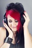 有耳机的美丽的女孩享受听到音乐的 免版税库存照片