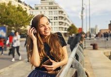 有耳机的美丽的女孩听到音乐的 库存照片