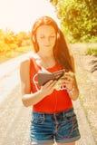 有耳机的美丽的妇女在持与金钱的路一本护照 库存图片