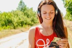 有耳机的美丽的妇女在持与金钱的路一本护照 免版税库存图片