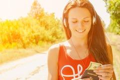 有耳机的美丽的妇女在持与金钱的路一本护照 免版税库存照片