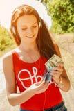 有耳机的美丽的妇女在持与金钱的路一本护照 免版税图库摄影