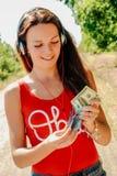 有耳机的美丽的妇女在持与金钱的路一本护照 库存照片