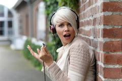 有耳机的美丽的白肤金发的妇女 免版税库存照片