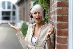 有耳机的美丽的白肤金发的妇女 库存照片